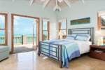 A refreshing, bright bedroom, including an oversized ottoman that converts to a single bed. Bath has a glass block-sided stall shower and access to the outdoor verandah overlooking the beach is through the large glass doors.